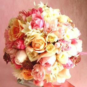 アイボリー~ピンク、オレンジの花色をまとめた可愛らしいクラッチブーケ